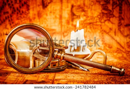 Vintage still life. Vintage magnifying glass lies on an ancient world map in 1565. - stock photo