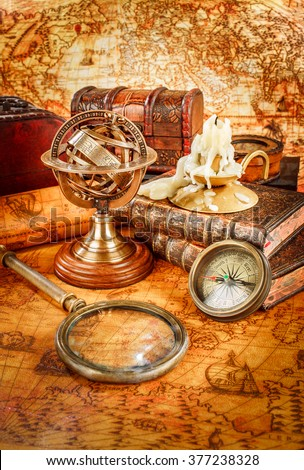 Vintage still life. Vintage magnifying glass lies, pocket watch, old book and armillary sphere on an ancient world map in 1565. - stock photo