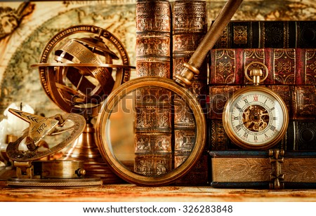 Vintage still life. Vintage magnifying glass lies, pocket watch, old book and astrolabe on an ancient world map in 1565. - stock photo