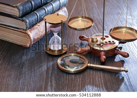 Vintage still life. Weight scale and tools on background with old books
