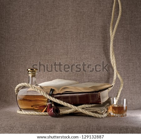 vintage still life with books, whiskey and tobacco pipe on the background fabric texture
