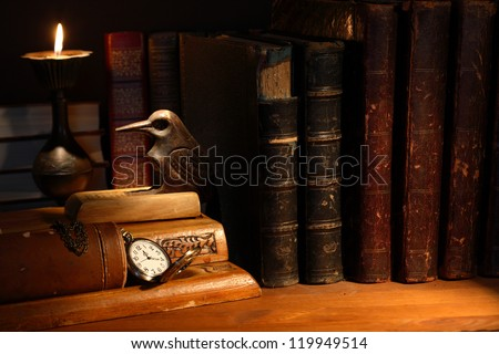 Vintage still life with desk set and ancient books near candle - stock photo