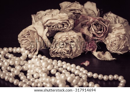 Vintage still life with faded roses and white pearls necklace close up - stock photo