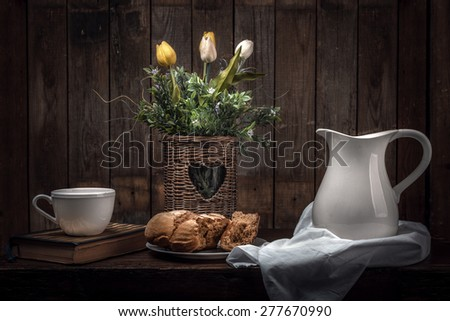 Vintage Still Life With Flowers, Bread,  Cup On Book, and A Pitcher Of Milk - stock photo