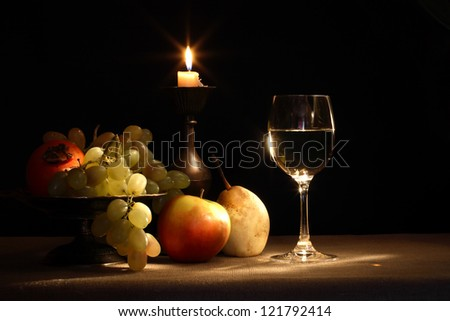 Vintage still life with fruits in bowl and wineglass near lighting candle - stock photo