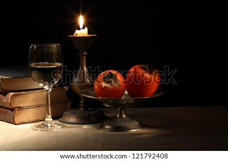 Vintage still life with fruits in bowl and wineglass near lighting candle and books - stock photo