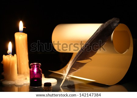 Vintage still life with ink pot and feather near scroll on dark background with candles