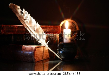 Vintage still life with old books and quill near lighting candle - stock photo