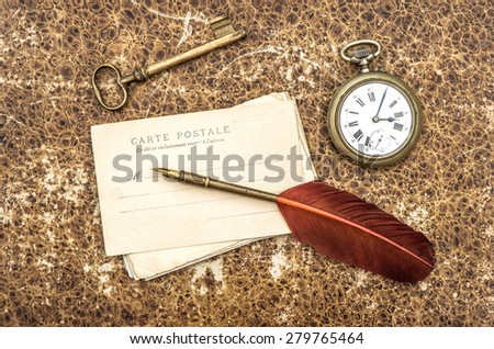 Vintage still life with old postcards, pocket watch, key and feather pen. Antique writing accessories