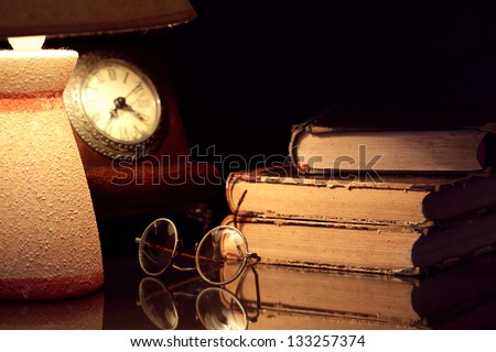 Vintage still life with old things: spectacles, books, clock and desk lamp