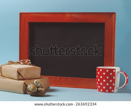 Vintage still life with quail eggs, gift boxes, red cup and black board for greeting text over blue background - stock photo