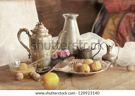 vintage still life with teapot, cups in glass-holders, lemon and honey - stock photo