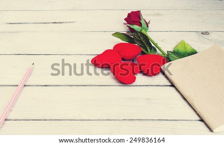 vintage story love,Hearts, roses, pencil and book on wood - stock photo