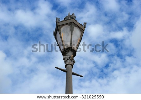 Vintage street lamp photographed large on the background of sky and clouds