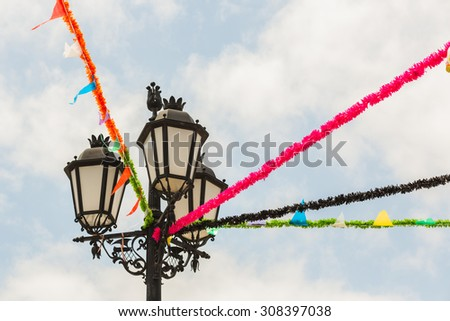 Vintage style black metal lamp post with opaque glass decorated for a festival, with bunting, in Portugal, Vila Real de Santo Antonio.