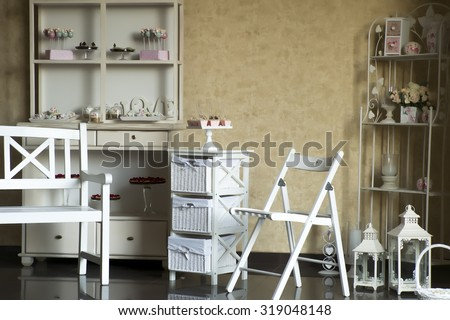 Vintage style candy store furnished white buffet and commode with sweets shelving decorated vases with roses small boxes candles candlesticks basket bench folding chair, horizontal photo - stock photo