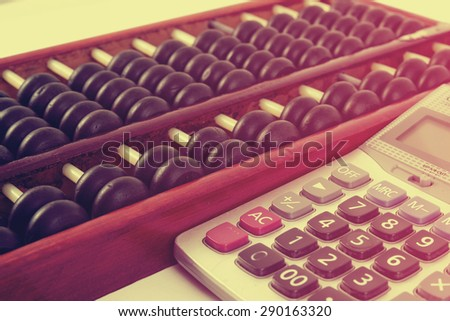 Vintage style - Close up of a wooden abacus beads and calculator. Selective focus, shallow depth of field. Wooden abacus on table wood texture background. - stock photo