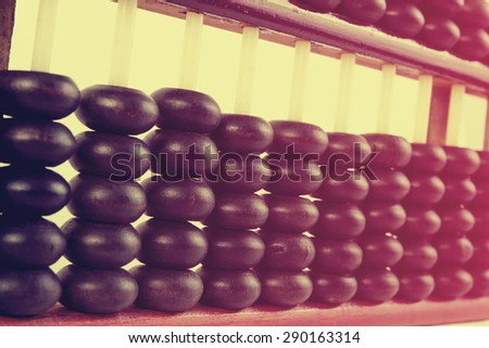 Vintage style - Close up of a wooden abacus beads. Selective focus, shallow depth of field. Wooden abacus on table wood texture background. - stock photo