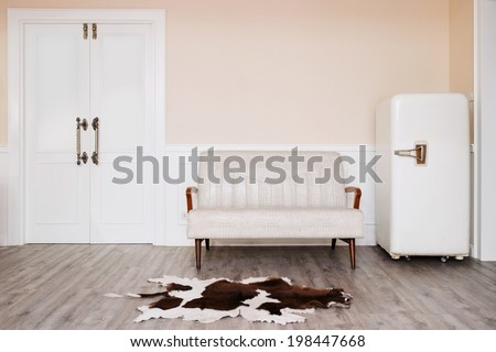 vintage style cozy room with old refrigerator, bench, carpet and door - stock photo
