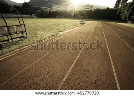 Vintage style - Empty vintage running track and old seats for the background with copy space with sunset.