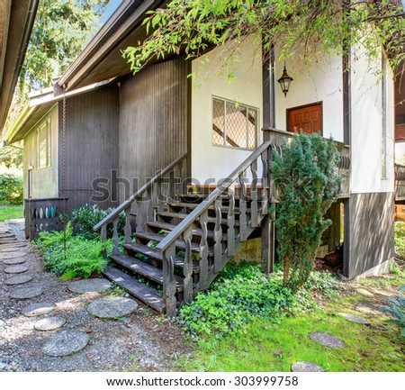 Vintage style entrance to home surrounded by greenery. - stock photo