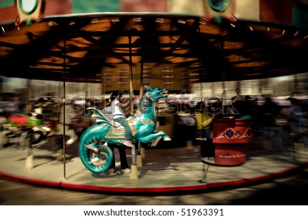 Vintage Style Girl riding blue dragon carousel - stock photo