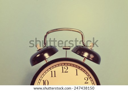 Vintage style, half alarm clock on a blue wall.