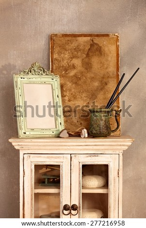 Vintage style home interior with show-case, frame and painting tools. - stock photo