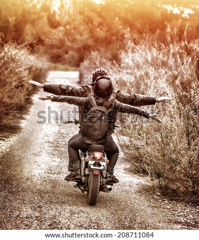 Vintage style image, rear view of two happy bikers riding on the road with raised up hands, active family enjoying journey on luxury extreme transport, freedom concept - stock photo