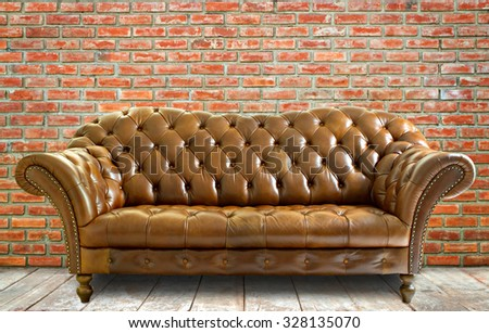 Vintage style  leather sofa with wooden floor and brick wall. - stock photo