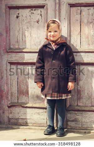 Vintage style. Little cute girl on the background of the old door. Selective focus. - stock photo