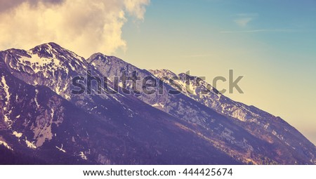 Vintage style looking view to rock snowbound alps mountains summits in clouds - stock photo
