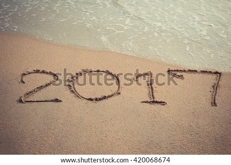 Vintage style 2017 message written in the sand at the beach background