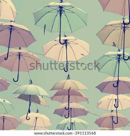 Vintage style photo of colorful umbrellas floating magically in the sunny blue sky above the street. Toned vintage colors   - stock photo