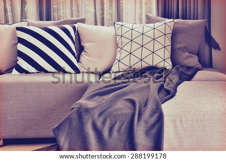 vintage style photo of L-shape sofa with varies pattern pillows in living corner - stock photo