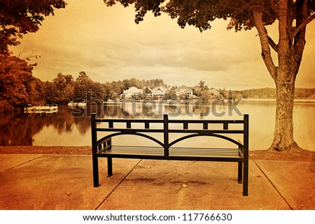 Vintage style photo of park with bench, trees and lake - stock photo