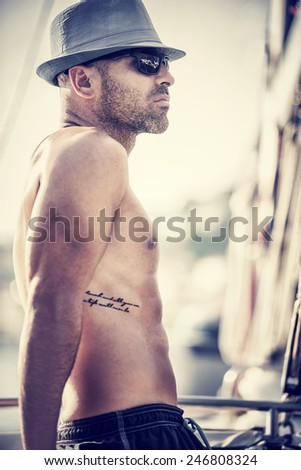 Vintage style photo of sexy shirtless sailor on sailboat, tanning man with stylish tattoo wearing trendy hat and sunglasses relaxation on luxury water transport - stock photo