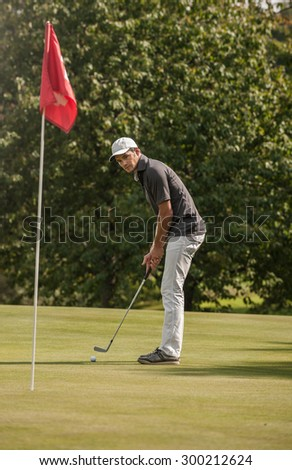 Vintage style, Portrait of a nice man surveying his putt on the fourteenth hole.  He is looking at the ball, wearing a cap and a sportswear outfit. A red flag is marking the hole - stock photo