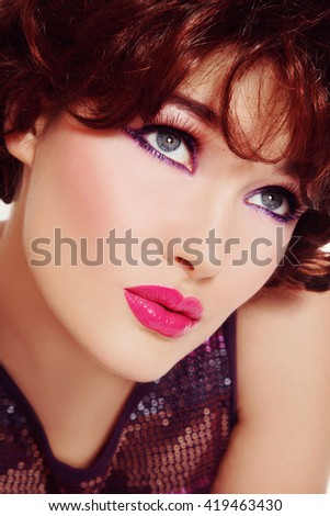 Vintage style portrait of young beautiful redhead woman with fancy winged eyes makeup