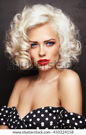 Vintage style portrait of young beautiful sexy blonde pin-up girl with curly hair and red lips over grunge background - stock photo