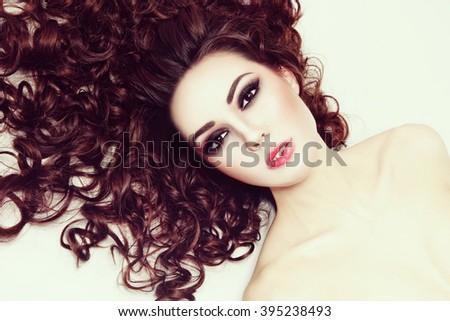 Vintage style portrait of young beautiful woman with fresh make-up and long curly hair