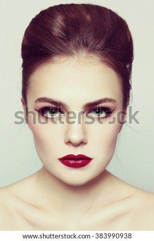 Vintage style portrait of young beautiful woman with hair bun and red lipstick