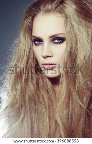 Vintage style portrait of young beautiful woman with long hair and smoky eyes make-up - stock photo