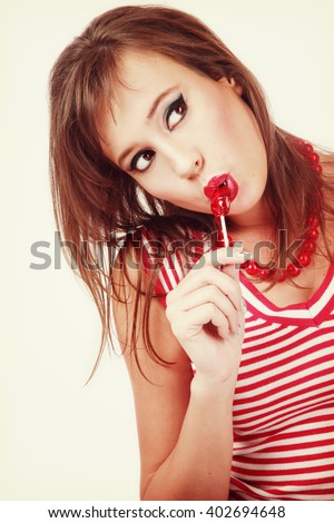 Vintage style portrait of young pretty girl with winged eyes make-up and lollipop