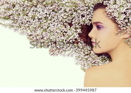 Vintage style profile portrait of young beautiful girl with bright make-up and lilac in her long hair