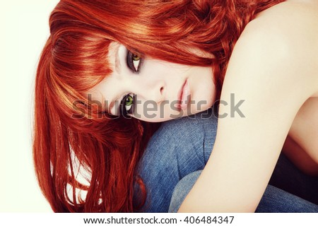 Vintage style shot of young slim beautiful redhead girl with smoky eyes make-up