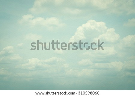 Vintage style sky with soft clouds in cool cyan color tone on watercolor paper textured background: Blurred nature background of retro cloudy sky with layers of puffy clouds on watercolour paper     - stock photo
