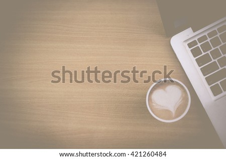 Vintage style with vignette filter of top view notebook (laptop) with coffee latte art heart on workspace of wooden table. Concept for workplace, freelance, blogger, social, programmer, background, - stock photo