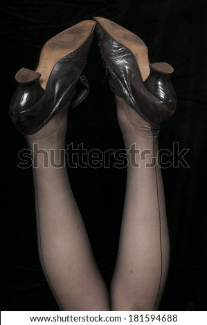 Vintage 1940 style woman in seamed stockings with her legs in the air, isolated on black background