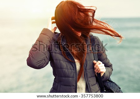 Vintage styled portrait of sensual ginger girl with long hairs poring new sea, windy weather, hairs close her face, sad mood, toned colors, cold autumn time. - stock photo